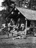1920s-1930s Couple Standing on Porch of Log Cabin Holding Pitcher Man Chopping Wood Fotografiskt tryck