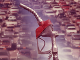 1970s Nozzle of Gasoline Pump with Traffic Background Photographic Print by Ewing Galloway