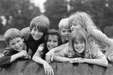 1970s-1980s Group of Six Boys and Girls Gathered Together on Large Playground Tire Photographic Print