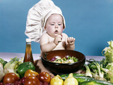 1960s Baby Making Salad Wearing Chef Hat with Variety of Fresh Ingredients Vegetables Photographic Print