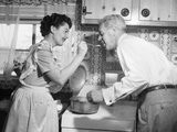 1950s Housewife in Kitchen Having Husband Taste Food on Stove Photographie