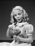 1940s Child Blond Girl Putting Money Coin into Piggy Bank Photographic Print