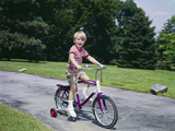 1960s-1970s Young Blond Boy Riding Bike with Training Wheels Lámina fotográfica