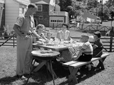 1950s Family in Backyard Cooking Hot Dogs Sitting at Picnic Table Photographic Print