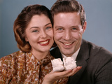 1960s Smiling Couple Holding Baby Shoes Photographic Print