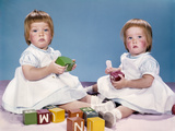 1950s-1960s Portrait Two Twin Baby Girls Wearing Dresses Playing with Toy Blocks Photographic Print