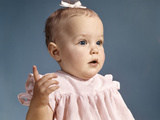 1960s Baby Girl Wearing Pink Dress with a Bow in Her Hair Pointing a Finger Photographic Print