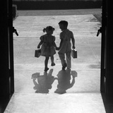 1950s Silhouetted Boy Girl Holding Hands Leaving School Doors Going Home Photographic Print