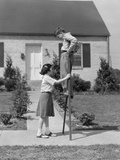 1950s Children Boy and Girl Playing with Stilts Standing Walking on Sidewalk Reproduction photographique
