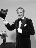1970s Smiling Man Magician Wearing Velvet Tuxedo White Gloves Pointing Magic Wand at Top Hat Photographic Print