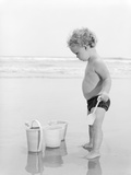1960s-1970s Child Toddler Standing in Sand Water Bucket Shovel Photographic Print