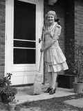1940s Smiling Woman Sweeping Porch Front Door Step with a Broom Fotografiskt tryck