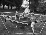1950s Mom and Kids Serving Dad in Hammock Photographic Print