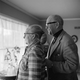1970s Senior Couple Looking Out a Window Photographic Print