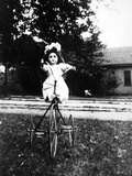 Large Play Doll Sits on a Period Tricycle, Ca. 1925 Photographic Print