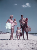 1950s Family Standing at Sandy Beach with Toys and Picnic Basket Photographic Print