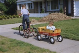 Boy Riding Tricycle and Towing Wagon Photographic Print by William Gottlieb