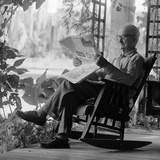 1970s Elderly Man Reading Newspaper on Porch in a Rocker Photographic Print