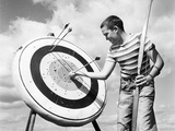 1960s Boy Jeans Striped T-Shirt Holding Bow and Pulling Arrow Out of Target Bull'S-Eye Photographic Print by H. Lefebvre