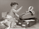 1960s Baby Seated in Small Chair Hitting Keys on Office Adding Machine on Top of Small File Drawers Photographic Print