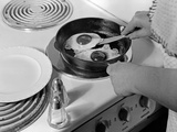 1940s-1950s Woman Hands Frying Eggs in Iron Skillet on Electric Stove Salt and Pepper Shakers Photographic Print