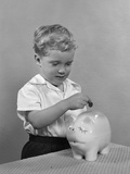 1950s Little Boy Putting Coin into Piggy Bank Photographic Print