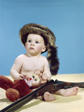 1960s Baby Boy Wearing Coonskin Cap with Stuffed Animal and Shotgun Gun Photographic Print