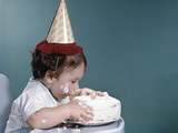 1960s Baby in Highchair Wearing Birthday Hat Eating Whole Birthday Cake Lámina fotográfica