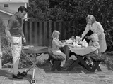 1960s Man Grilling Steak with 2 Daughters Seated at Picnic Table and Wife Standing Serving Food Photographie
