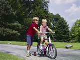 1960s-1970s Boy Helping Little Brother Ride Two Wheel Bicycle with Training Wheels Photographic Print