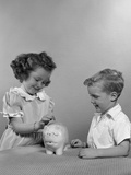 1950s Little Girl and Boy Putting Coin into Piggy Bank Photographic Print