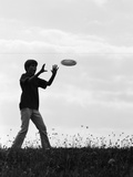 1960s-1970s Silhouette of Boy Catching Frisbee in Field Photographic Print