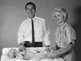 1960s Smiling Mother and Father with Twin Babies on Diaper Changing Table Photographic Print