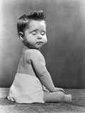 1940s-1950s Baby Seated with Back to Camera Turning Head to Viewer with Eyes Closed Photographic Print