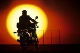 1980s Silhouette of Anonymous Man on Motorcycle Driving Toward Rising Setting Sun Reprodukcja zdjęcia