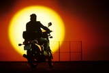 1980s Silhouette of Anonymous Man on Motorcycle Driving Toward Rising Setting Sun Photographic Print