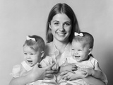 1970s Smiling Mother Holding Female Twins with Bows in Hair One with Each Arm Photographic Print