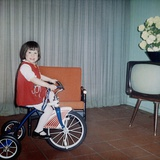 Young Girl Rides Her New Tricycle in the House, Ca. 1967 Photographic Print