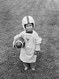 1950s Boy Standing in Grass Wearing Oversized Shirt and Helmet Holding Football Photographic Print by H. Lefebvre