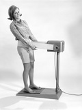 1960s Smiling Young Woman Standing on Weight Reducing Vibrating Exercise Machine Photographic Print