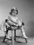 1960s Little Girl Putting on Shoes Sitting on Chair Photographic Print