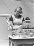 1930s Woman in Kitchen Wearing Apron Making Breakfast Pouring Water into Coffee Pot Photographic Print by H. Armstrong Roberts