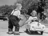 1950s Little Boy Playing Gas Station Pouring Water into Toy Car for Little Girl Papier Photo par H. Armstrong Roberts