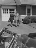 Couple Carrying Luggage Walking Towards Convertible Car in Driveway Photographic Print by H. Armstrong Roberts