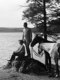 1930s Man Standing on Rock Lakeside Holding Reins of Two Horses with Woman Seated Beside Reproduction photographique par H. Armstrong Roberts