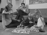 Family Mother Kids Playing Board Game Living Room Floor Father Reading Newspaper Photographie par H. Armstrong Roberts