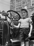 1930s Smiling Boy Standing Next to Fire Engine Wearing Firemans Hat Photographic Print by H. Armstrong Roberts