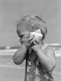 1950s Blond Toddler Girl Listening to Ocean in a Seashell Wearing Teddy Bear Bathing Suit Stampa fotografica di H. Armstrong Roberts