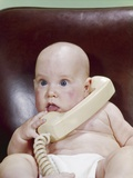 1960s Chubby Baby Sitting in Leather Office Chair Talking on Telephone Reproduction photographique par H. Armstrong Roberts