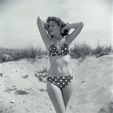 1950s Brunette Bathing Beauty in Polka Dot Bikini Standing in Sand with Hands Behind Head Photographic Print by H. Armstrong Roberts